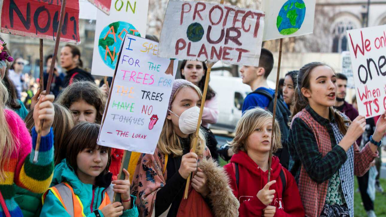 Young people holding placards at climate protest